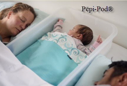 Mother and father sleeping with their baby in a Pepi-pod