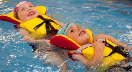 Two young children swimming in a pool wearing lifejackets