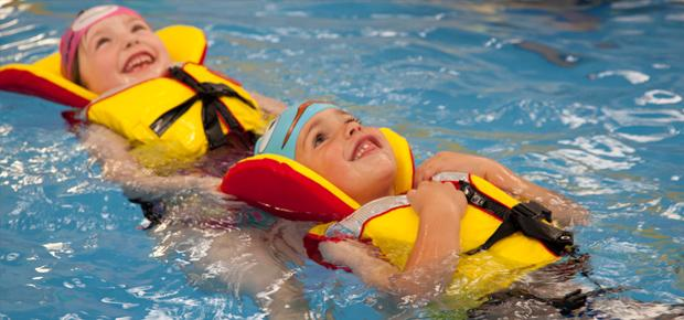 Two young smiling girls wearing life jackets and floating on their backs in a swimming pool