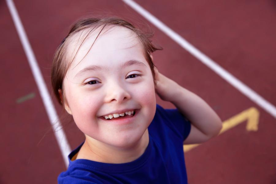 Young girl with disability smiling to camera while at the track in a stadium