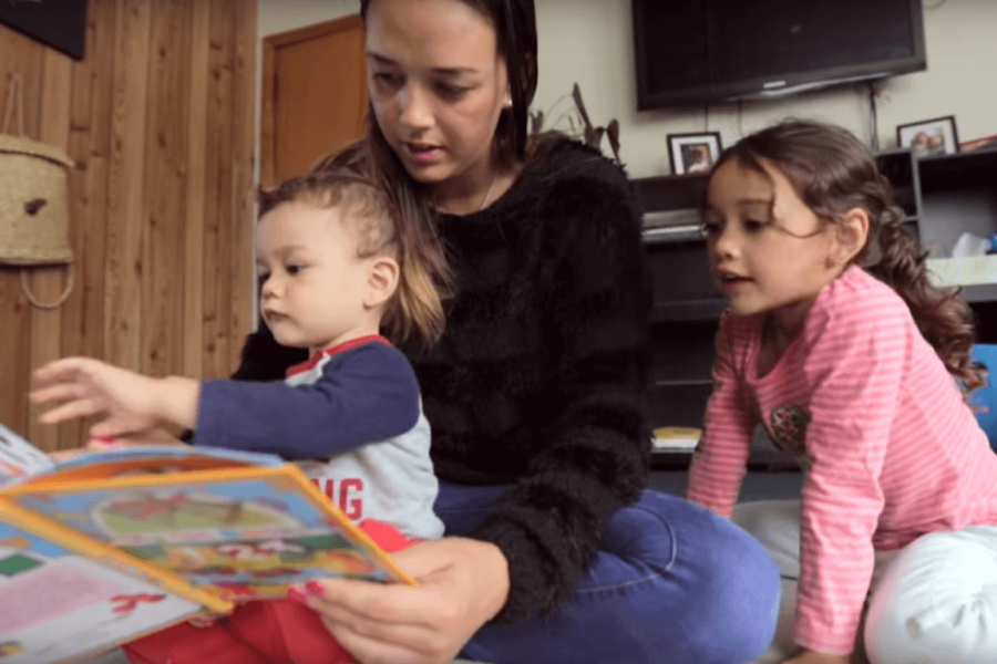 A mother reading to her 2 children