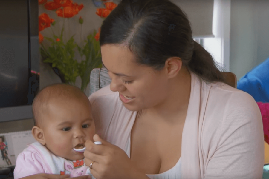 Mother with her baby on her lap, giving her baby a spoon of pureed baby food
