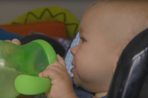 Baby holding cup of water