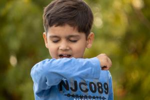 Boy coughing into his elbow