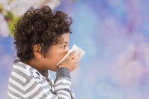 Boy with a virus blowing his nose into a tissue