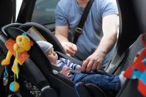 Father fastening his baby son in to a car seat