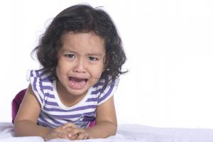 A child leaning forward and crying in pain