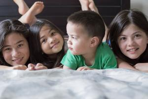 Group of children lying on a bed