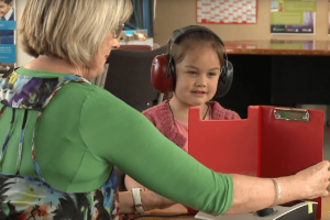 A vision hearing technician testing a young girl with headphones on