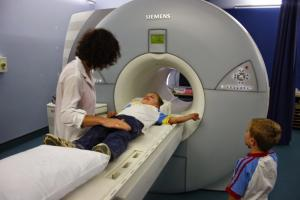 Child going into MRI scanner with radiologist standing over child and sibling looking on