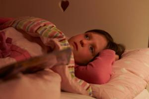 Worried young girl lying in bed awake at night